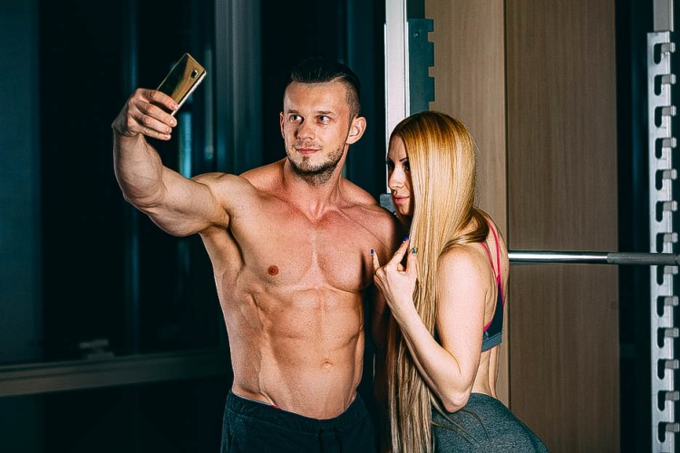 Young couple exercising in gym with weights man, selfie, Snapshots on the phone